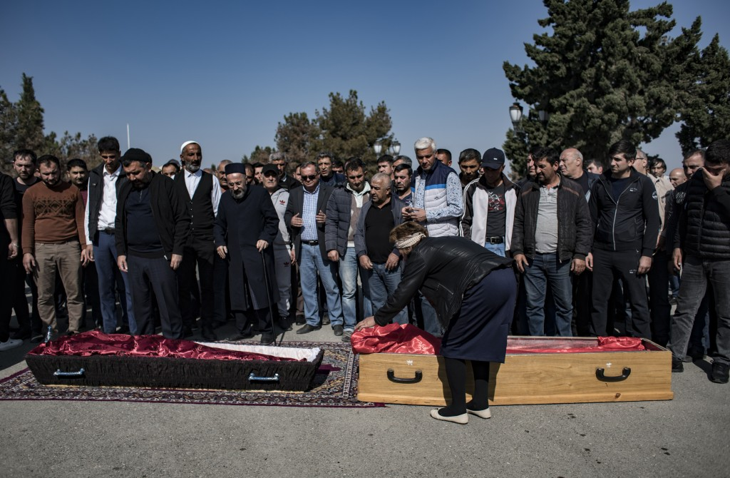 People attend the funeral prayers for three members of an Azerbaijani Turkish family, Royal Shahnazarov, his wife Zuleyxa Shahnazarova and their one-y...