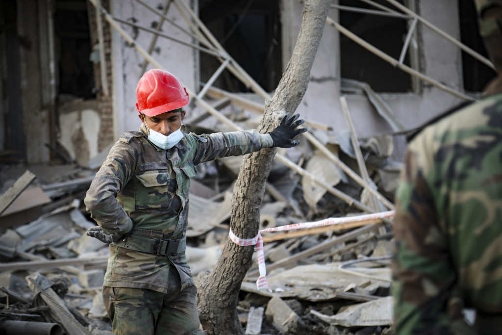 An Azerbaijan's soldier wearing a face mask to protect against coronavirus stands near a destroyed house in a residential area that was hit by rocket ...