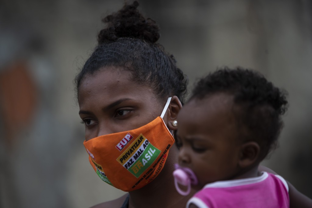 Carolaine Rocha, 22, holds her son while waiting to receive donated food from Petrobras workers and the oil workers union via the Tankers' Campaign th...
