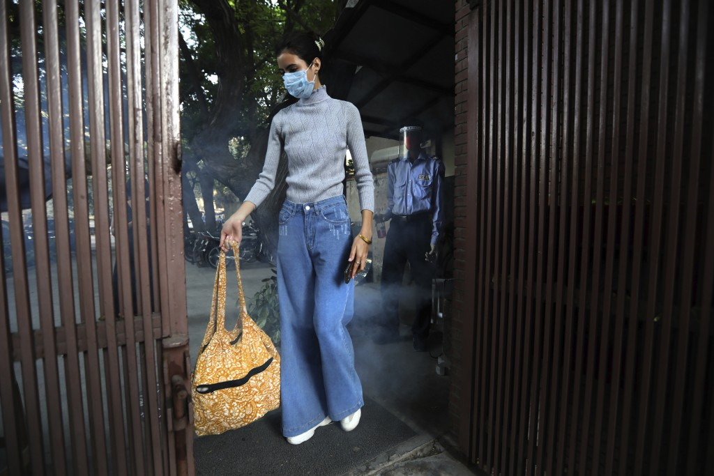 A model gets herself sanitized before entering the office of the Fashion Development Corporation of India (FDCI) in preparation for the Lotus make-up ...