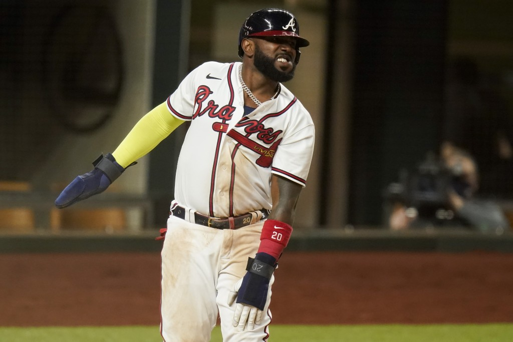 Atlanta Braves' Marcell Ozuna watches after getting called out at home after leaving third early during the third inning in Game 5 of a baseball Natio...
