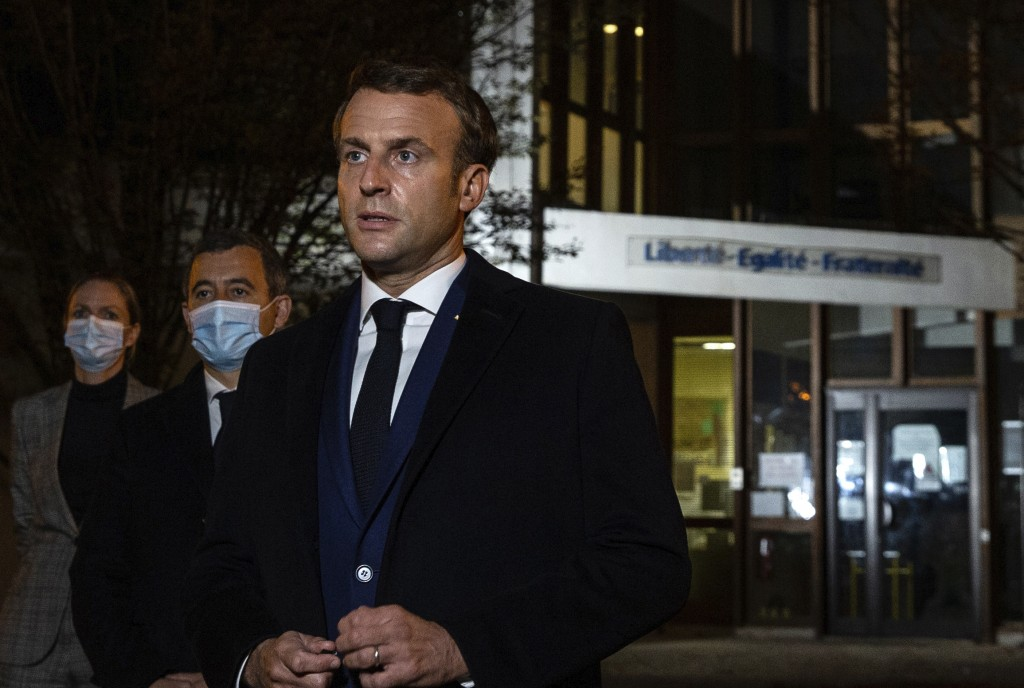 French President Emmanuel Macron, flanked by French Interior Minister Gerald Darmanin, second left, speaks in front of a high school Friday Oct.16, 20...