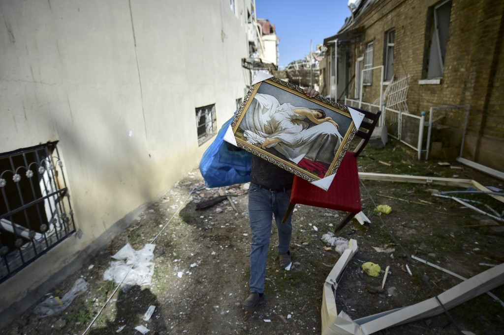 A man carries belongings from his damaged house two days after shelling by Armenian's artillery during fighting over the separatist region of Nagorno-...