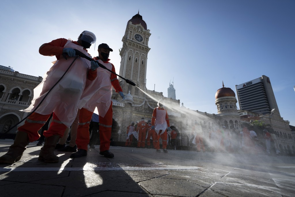 City hall workers spray a disinfectant Merdeka Square, or independence square, situated in front of the Sultan Abdul Samad Building, background, in Ku...