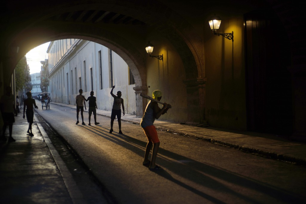Wearing masks as a precaution against the spread of the new coronavirus, children play baseball in Old Havana, Cuba, Monday, Oct. 12, 2020. Cuba relax...