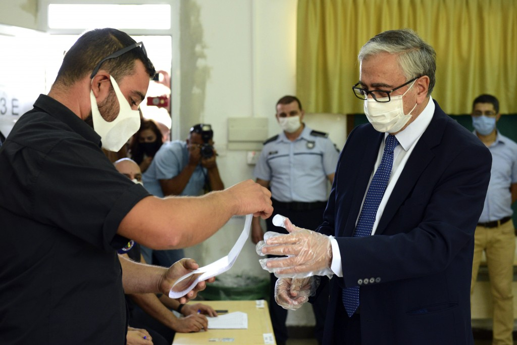 In this photo taken on Sunday, Oct. 11, 2020, Turkish Cypriot leader and candidate Mustafa Akinci casts his ballot at a polling station during the Tur...