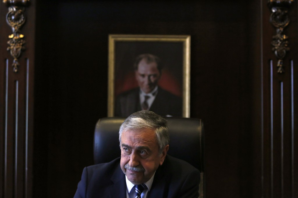 FILE - In this Monday, April 4, 2016 file photo, Turkish Cypriot leader Mustafa Akinci is seen at his office in front of the portrait of the Turkish R...
