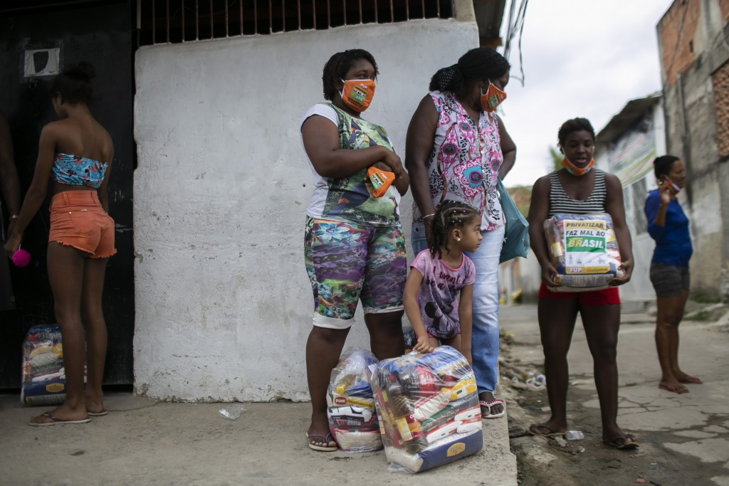 Residents receive donated food from Petrobras workers and the oil workers union via the Tankers' Campaign that provide a supplement for the poor caugh...