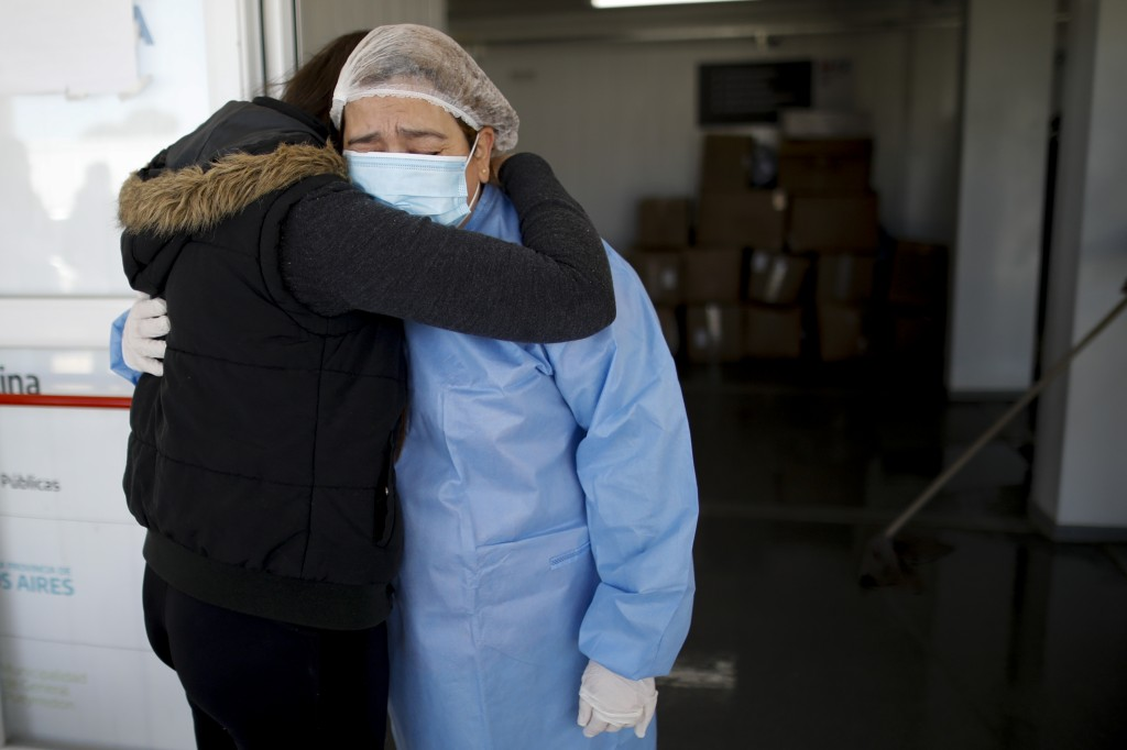 COVID-19 patient Claudia Brigando, right, embraces her daughter Marina Peralta, after being discharged from a hospital in Mar del Plata, Argentina, Sa...