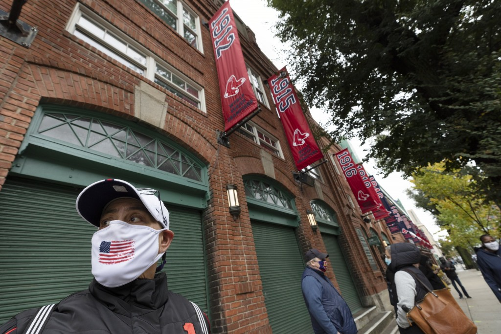 Karen Russell waits in line for early voting to open at Fenway Park, Saturday, Oct. 17, 2020, in Boston. (AP Photo/Michael Dwyer)