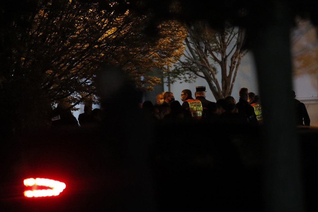 French rescue workers and police officers gather outside a high school after a history teacher who opened a discussion with students on caricatures of...