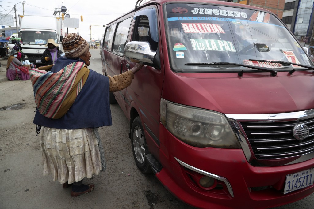 A woman begs for alms in El Alto, Bolivia, Saturday, Oct. 17, 2020. Sunday's presidential election gives Bolivians a chance for a political reset as t...