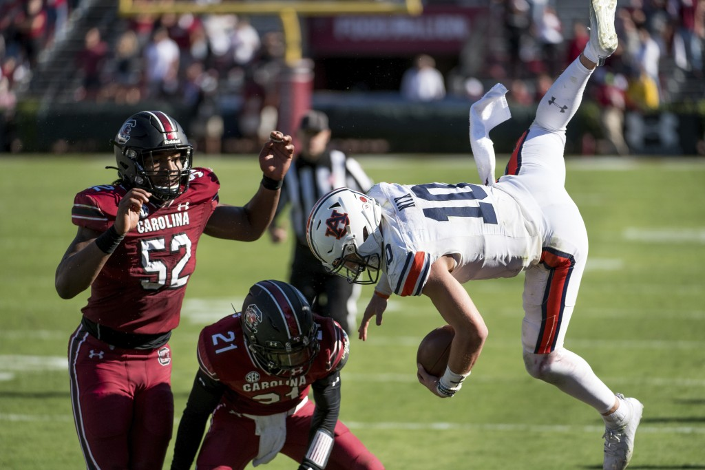 Auburn quarterback Bo Nix (10) is knocked out of bounds by South Carolina defensive back Shilo Sanders (21) and Kingsley Enagbare (52) during the seco...