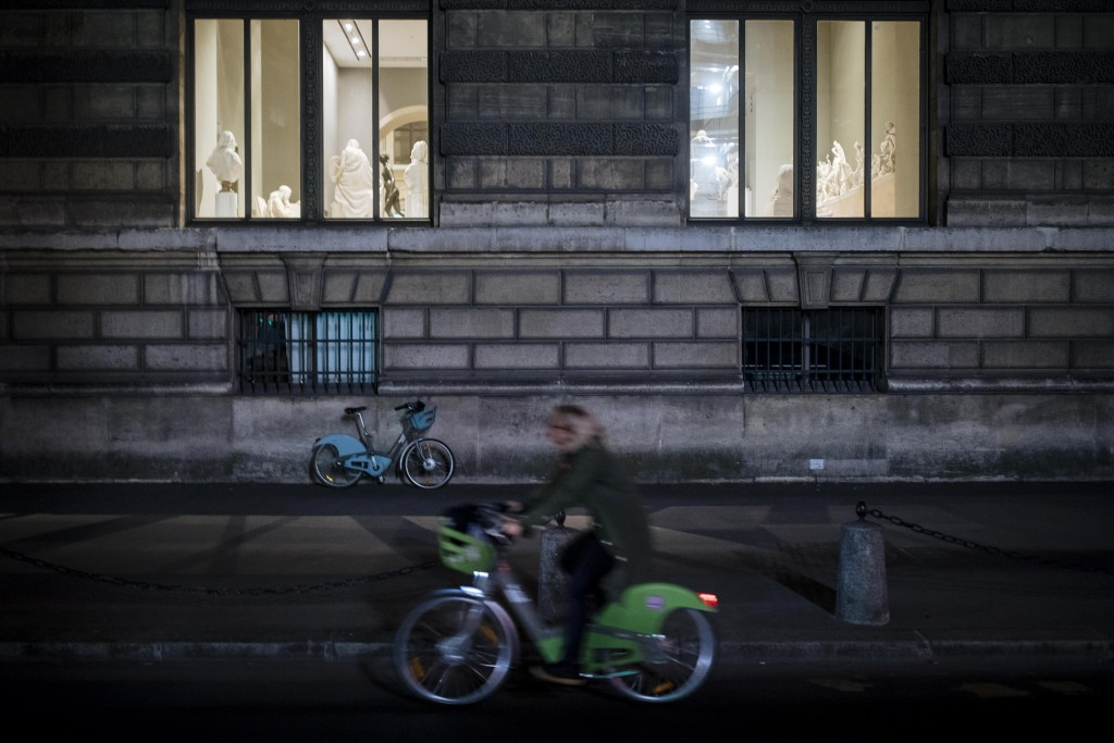 A woman rides a bike as she passes by the Louvre museum during curfew in Paris, Saturday, Oct. 17, 2020. French restaurants, cinemas and theaters are ...