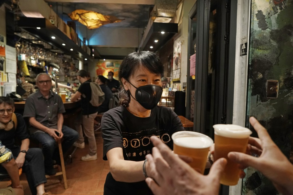 In this Oct. 9, 2020 photo, a bartender serves beers at Club 71 in Central, a business district of Hong Kong. The bar known as a gathering place for p...