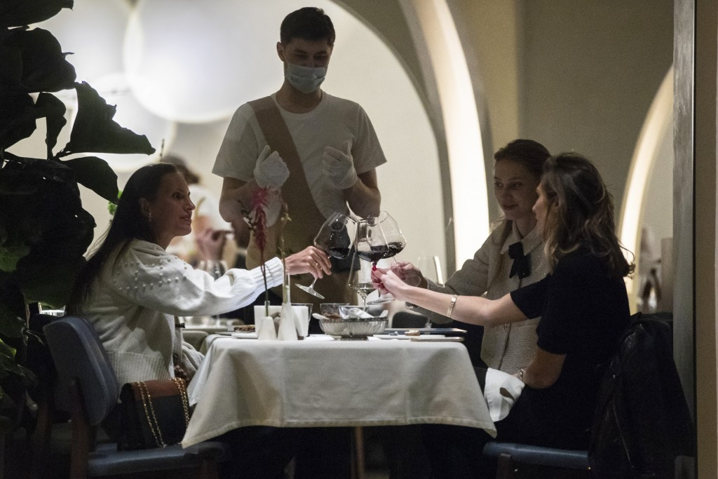 A waiter wearing a face mask and gloves to protect against coronavirus, serve customers in a restaurant at Patriarshiye Prudy, a hip restaurant and ba...