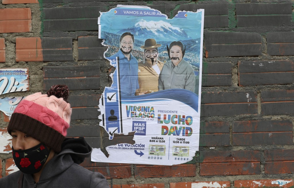A child walks past a defaced election poster promoting presidential candidate Luis Arce representing the Movement Towards Socialism political party be...
