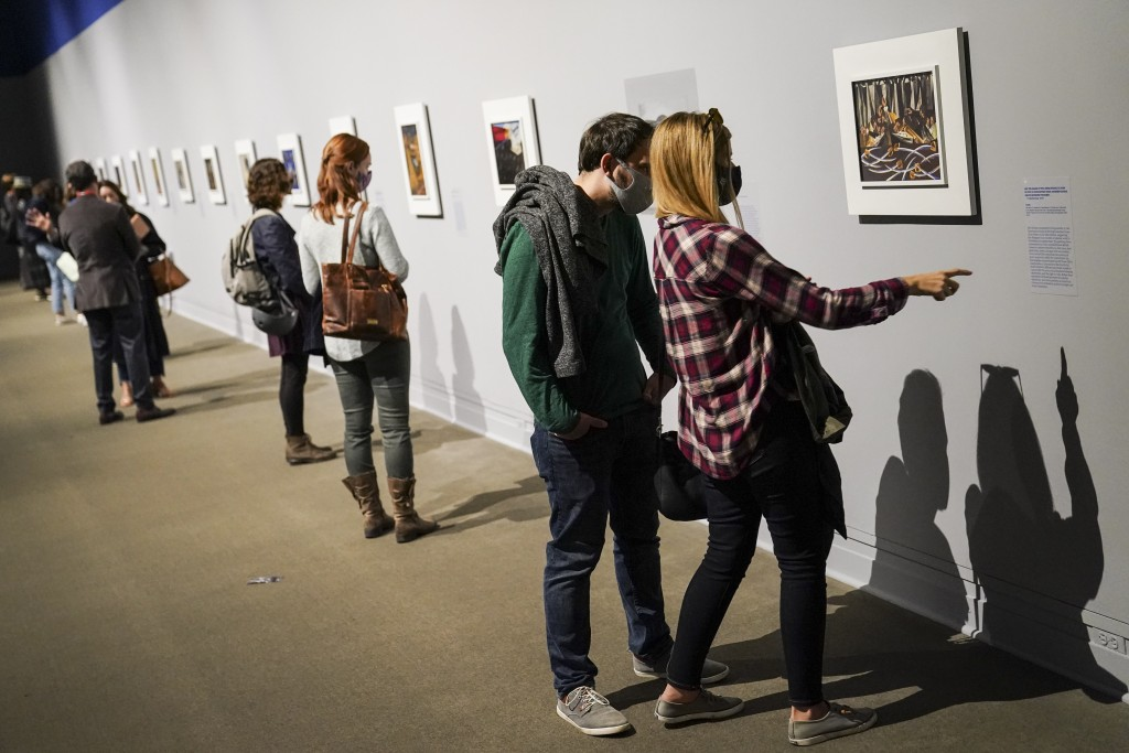 """Visitors wearing protective masks observe COVID-19 prevention protocols as they browse the """"Jacob Lawrence: The American Struggle"""" exhibition at the M..."""