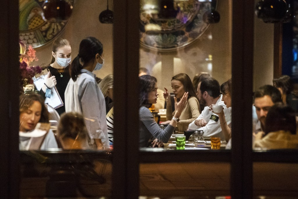 Customers sit in a restaurant at Patriarshiye Prudy, a hip restaurant and bar district in Moscow, Russia, late Friday, Oct. 16, 2020. The outbreak in ...