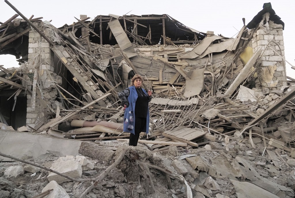 Home owner, Lida Sarksyan, stands near her house destroyed by shelling from Azerbaijan's artillery during a military conflict in Stepanakert, the sepa...