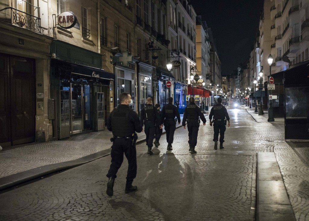Police patrol in the streets as the curfew starts in Paris, Saturday, Oct. 17, 2020. French restaurants, cinemas and theaters are trying to figure out...