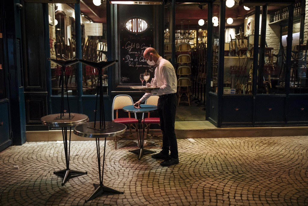 A waiter closes a bar terrace in Paris, Saturday Oct. 17, 2020. French restaurants, cinemas and theaters are trying to figure out how to survive a new...