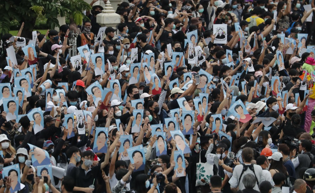 Pro-democracy demonstrators hold posters of protest leaders who have been arrested, during an anti-government protest at Victory Monument in Bangkok, ...