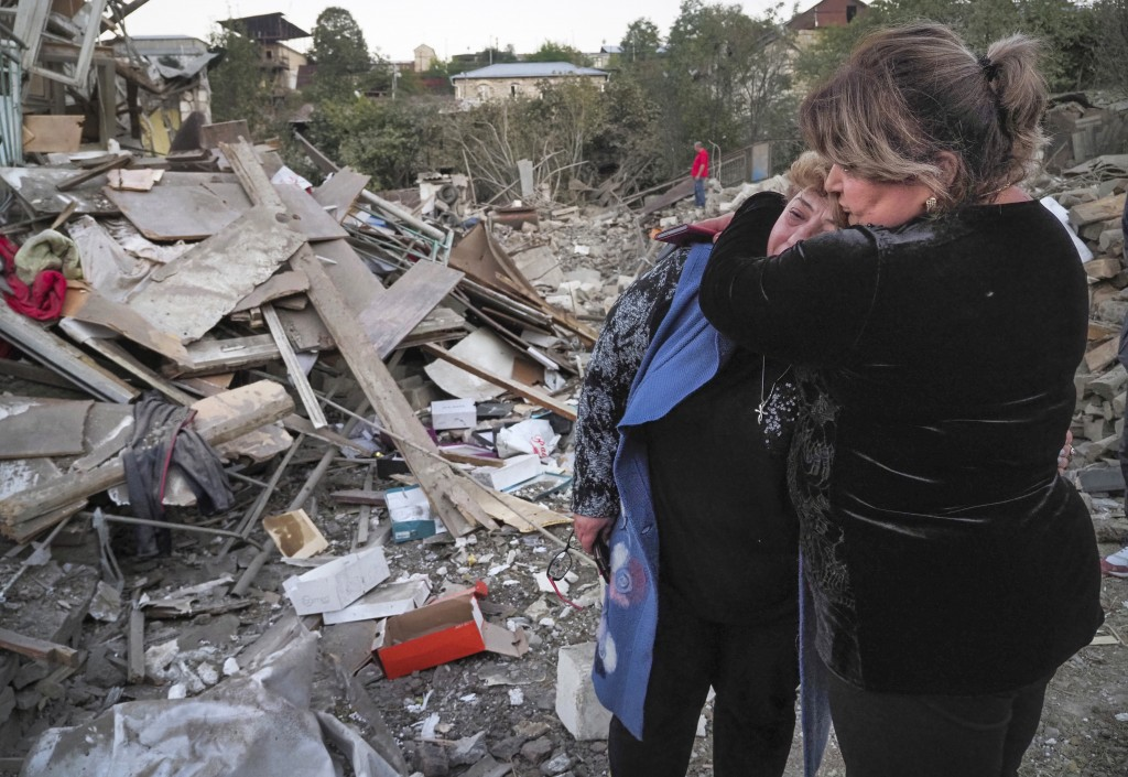 A neighbour comforts home owner, Lida Sarksyan, left, near her house destroyed by shelling from Azerbaijan's artillery during a military conflict in S...