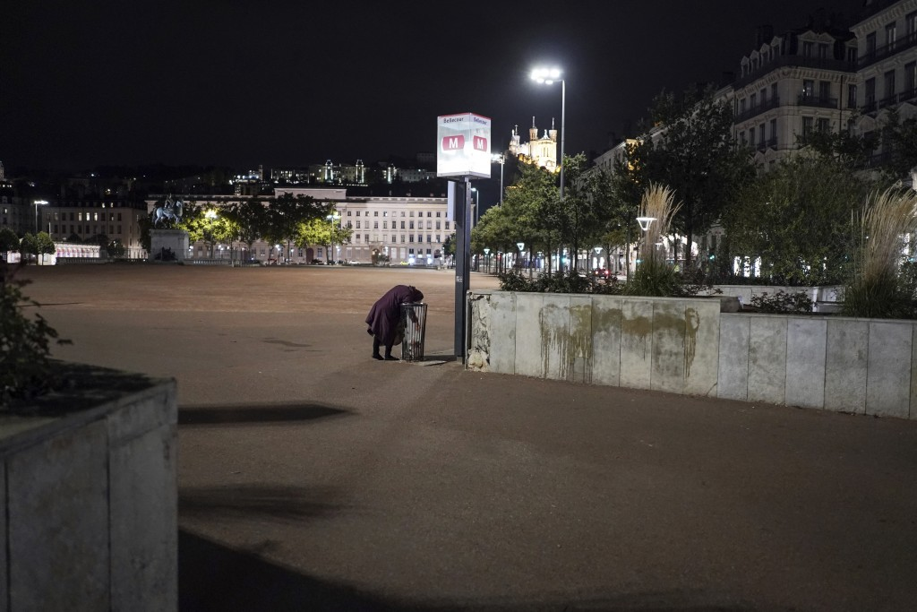 A homeless woman looks for food in the empty center of Lyon, central France, Saturday, Oct. 17, 2020. France is deploying 12,000 police officers to en...