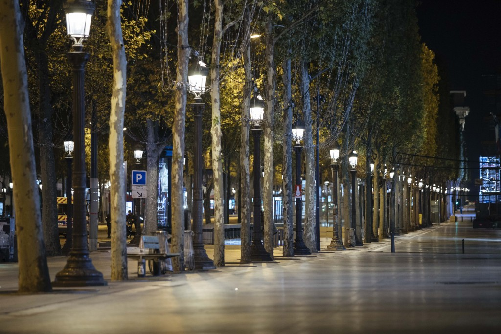 Champs-Elysees avenue is empty during curfew in Paris, Saturday, Oct. 17, 2020. French restaurants, cinemas and theaters are trying to figure out how ...