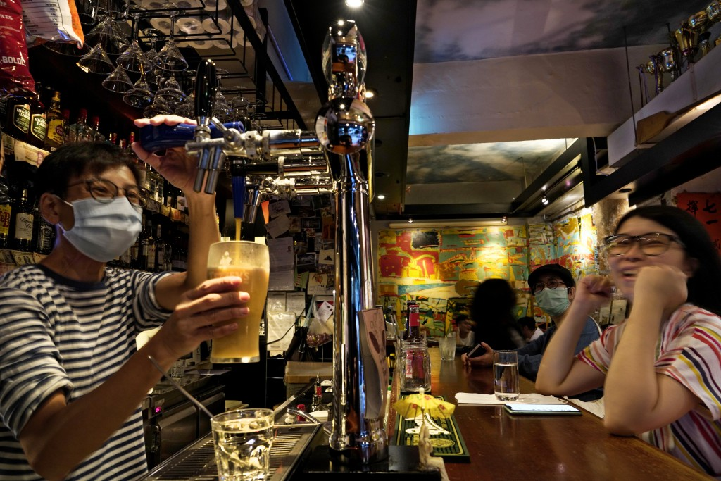 In this Oct. 7, 2020 photo, an employee serves a beer to a customer at Club 71 in Hong Kong. The bar known as a gathering place for pro-democracy acti...