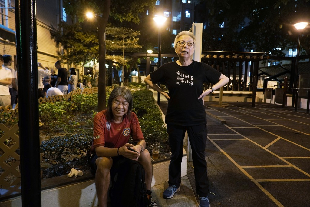 In this Oct. 9, 2020 photo, Grace Ma, right, chats with pro-democracy activist Leung Kwok-hung outside her bar Club 71 in Hong Kong. The bar known as ...