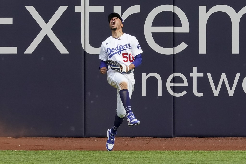 Los Angeles Dodgers right fielder Mookie Betts celebrates after robbing Atlanta Braves' Marcell Ozuna of a home during the fifth inning in Game 6 of a...