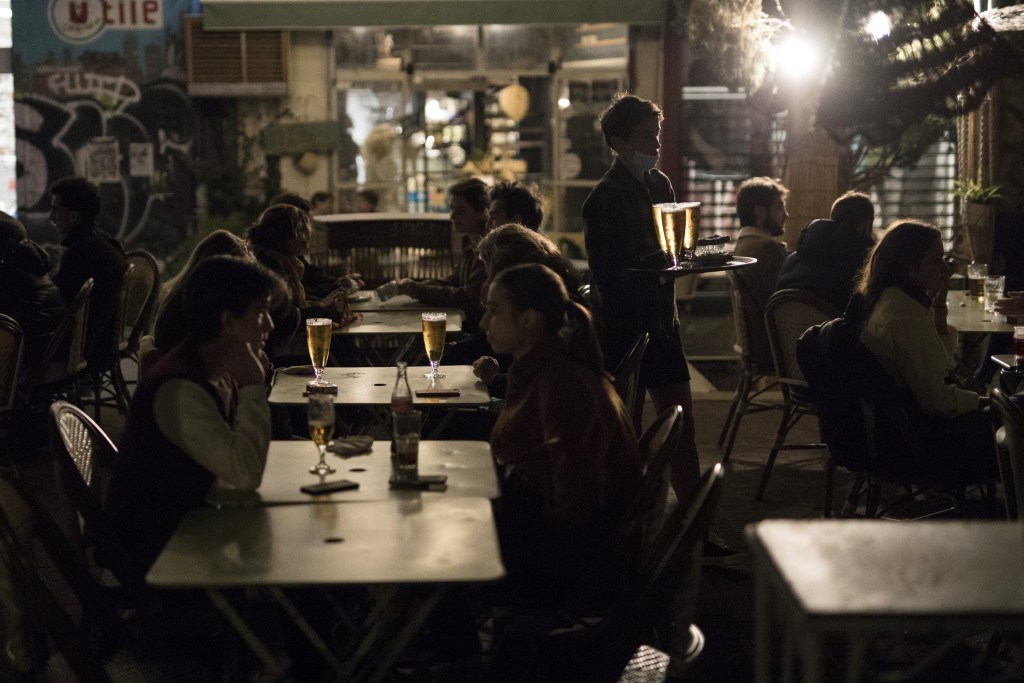 People enjoy drinks at a bar terrace in Marseille, southern France, Saturday, Oct. 17, 2020. France is deploying 12,000 police officers to enforce a n...