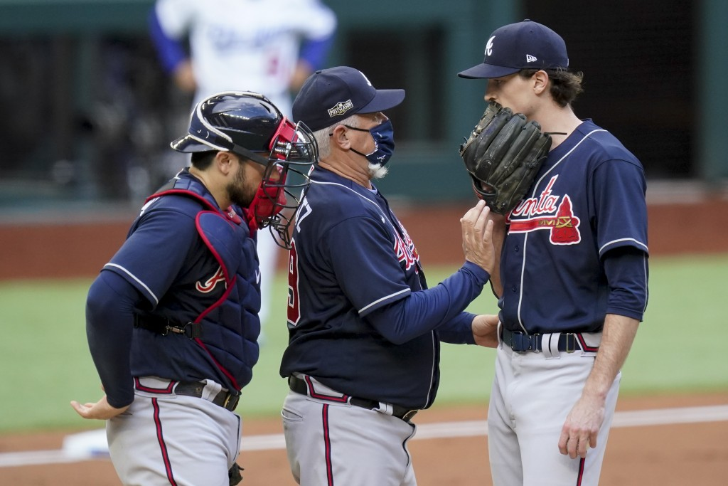 Atlanta Braves manager Brian Snitker talks with starting pitcher Max Fried during the first inning in Game 6 of a baseball National League Championshi...