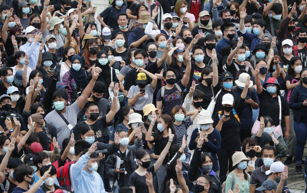 Pro-democracy demonstrators flash three-fingered salute during an anti-government protest, at Victory Monument in Bangkok, Thailand, Sunday, Oct. 18, ...