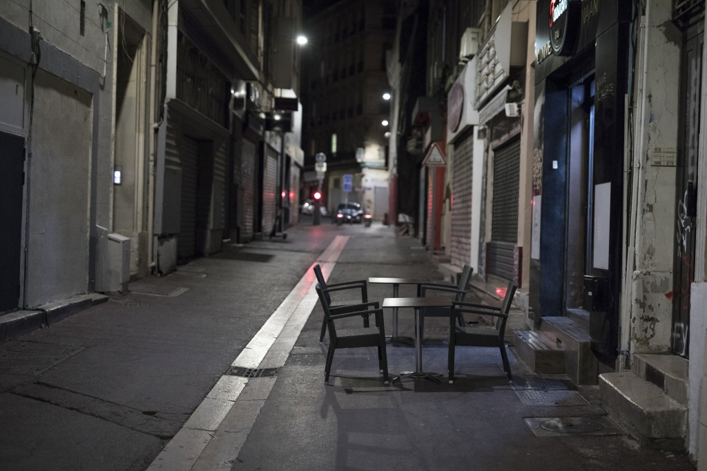 Tables sit empty in Marseille, southern France, Saturday, Oct. 17, 2020. France is deploying 12,000 police officers to enforce a new curfew that came ...
