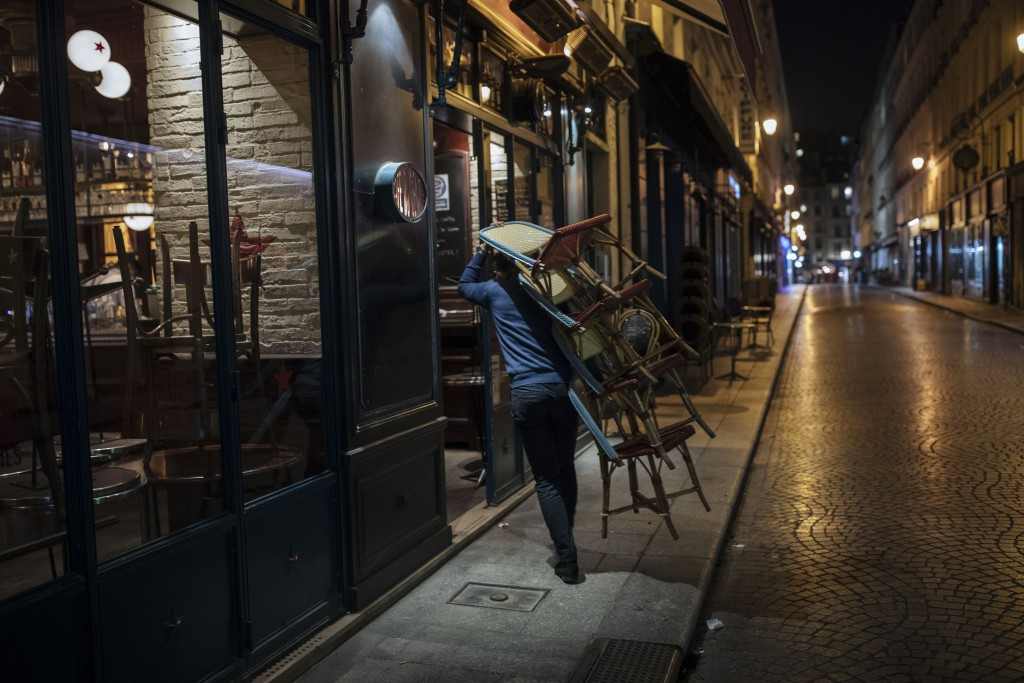 A waiter closes a bar terrace in Paris, Saturday, Oct. 17, 2020. French restaurants, cinemas and theaters are trying to figure out how to survive a ne...