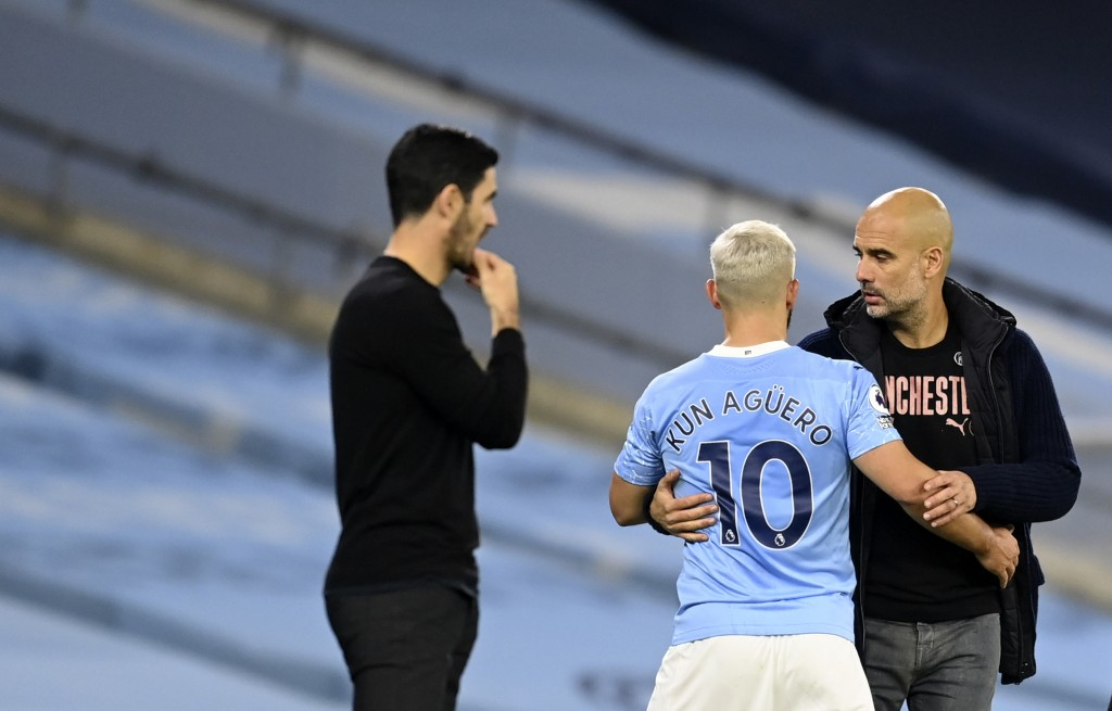 Manchester City's Sergio Aguero, centre, speaks with Manchester City's head coach Pep Guardiola after being substituted during the English Premier Lea...