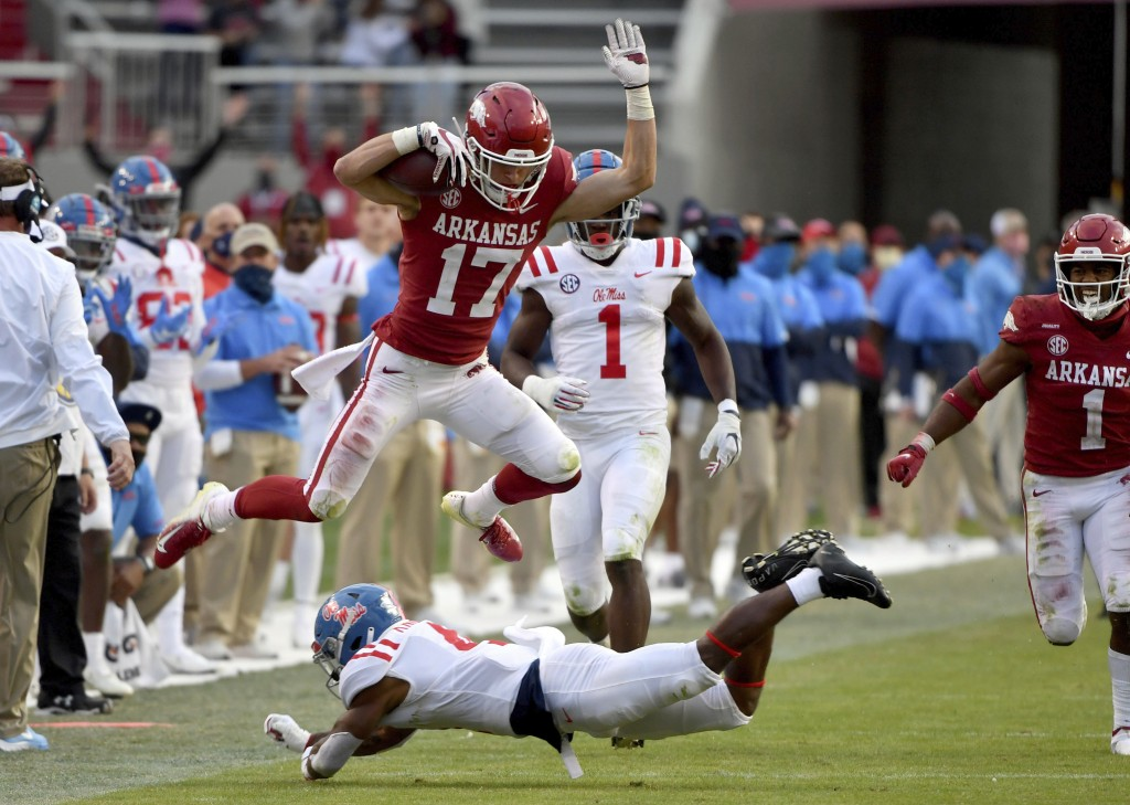Arkansas defensive back Hudson Clark (17) leaps over Mississippi running back Tylan Knight (4) as he returns an interception during the second half of...