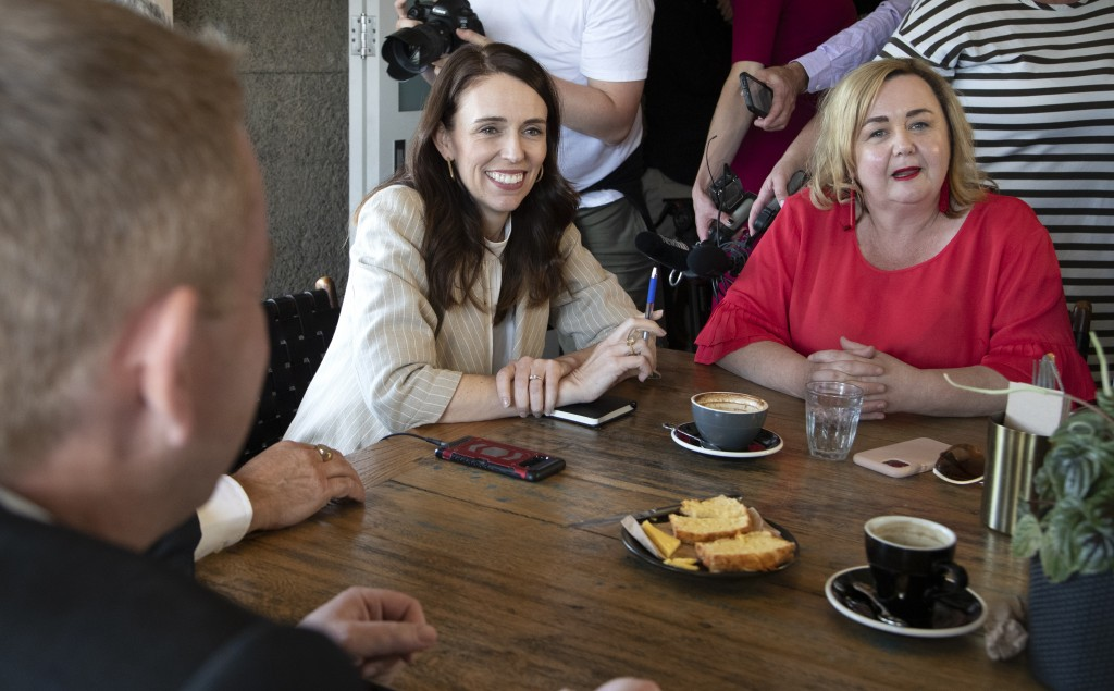 New Zealand Prime Minister Jacinda Ardern, left, and Megan Woods talk with colleagues at a cafe in Auckland, New Zealand, Sunday, Oct. 18, 2020. Arder...