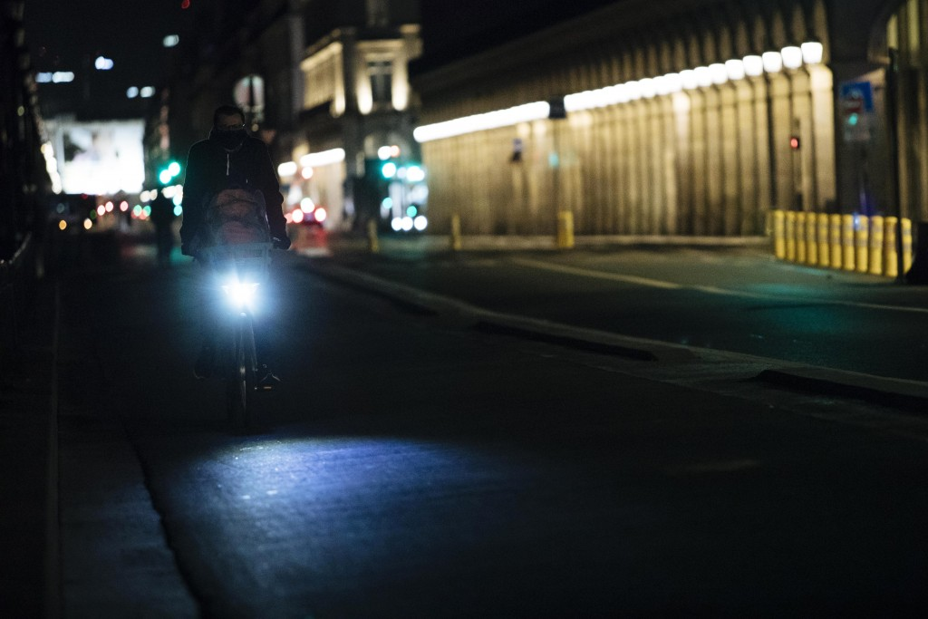A man rides a bike on Rivoli street during curfew in Paris, Saturday, Oct. 17, 2020. French restaurants, cinemas and theaters are trying to figure out...