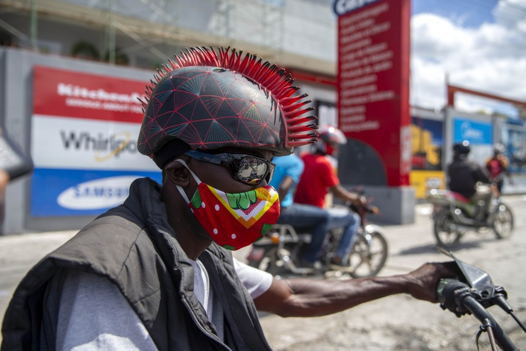 A motorcyclist wears a protective face mask and a mohawk helmet as he takes part in a protest to demand the resignation of President Jovenel Moise in ...