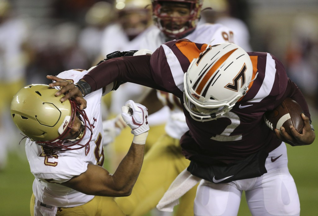 Virginia Tech quarterback Hendon Hooker, right, stiff arms Deon Jones, left, of Boston College in the first half of an NCAA college football game in B...