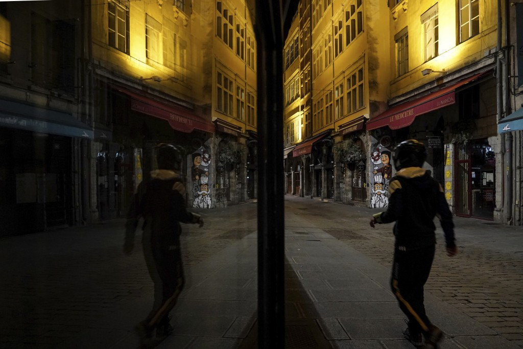 A man walks in the empty center of Lyon, central France, Saturday, Oct. 17, 2020. France is deploying 12,000 police officers to enforce a new curfew t...