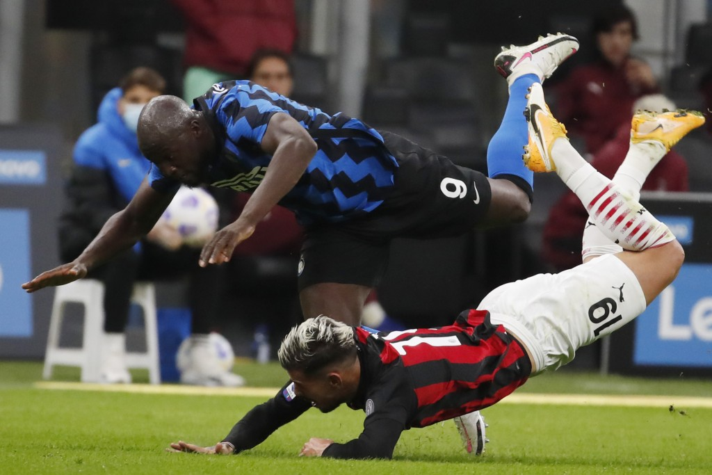 AC Milan's Theo Hernandez, bottom, and Inter Milan's Romelu Lukaku vie for the ball during the Serie A soccer match between Inter Milan and AC Milan a...