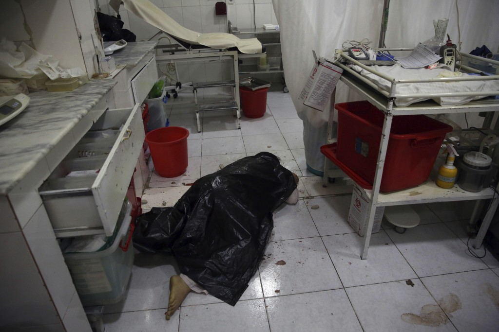 File - In this Tuesday, May 12, 2020 file photo, body of a woman lies on the floor of a delivery room in a maternity hospital, in Kabul, Afghanistan. ...
