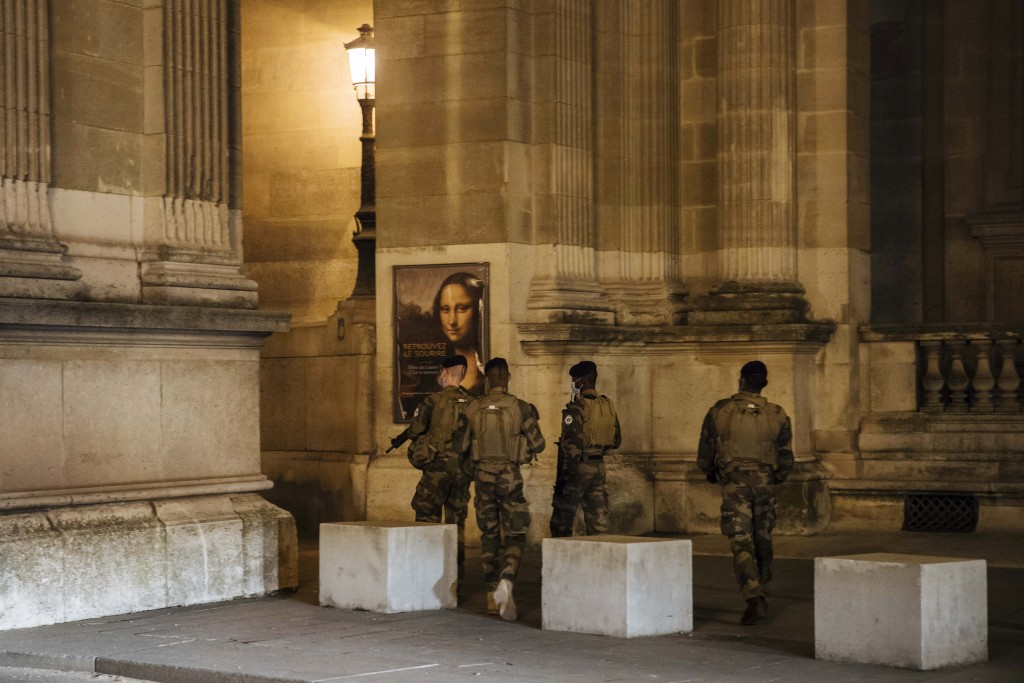 Military patrol near the Louvre museum during curfew in Paris, Saturday, Oct. 17, 2020. French restaurants, cinemas and theaters are trying to figure ...