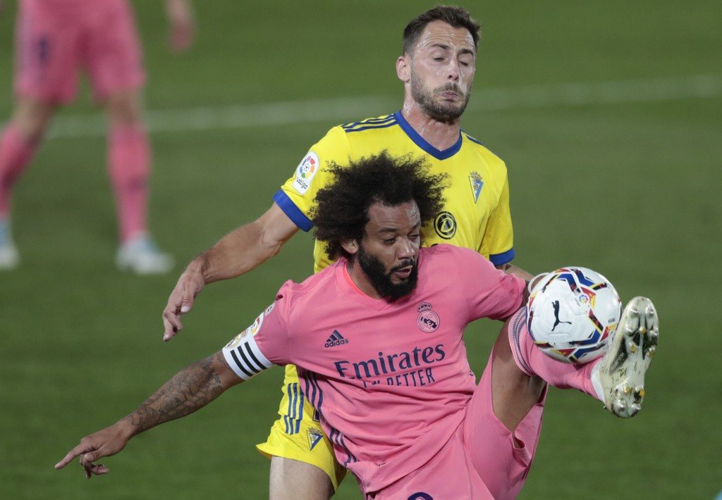 Real Madrid's Marcelo, front, and Cadiz's Filip Malbasic fight for possession during the Spanish La Liga soccer match between Real Madrid and Cadiz at...