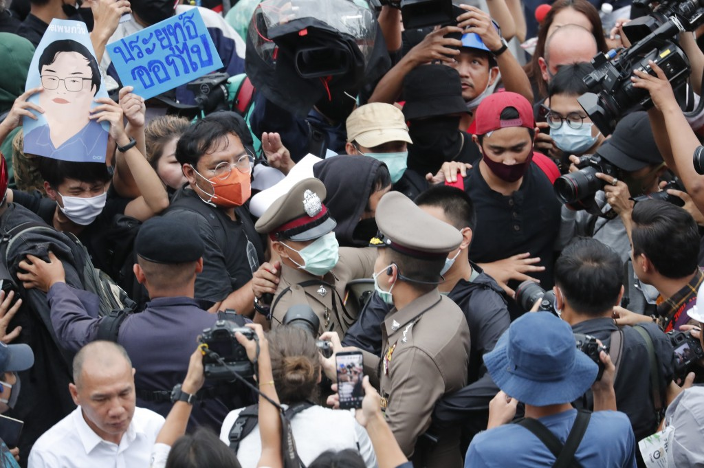 Police officials scuffle with pro-democracy demonstrators during an anti-government protest at Victory Monument in Bangkok, Thailand, Sunday, Oct. 18,...